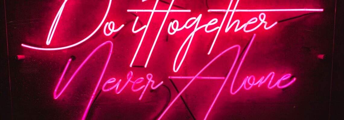 "Pink neon on a black background. Text reads, ""Do it together, never alone."""