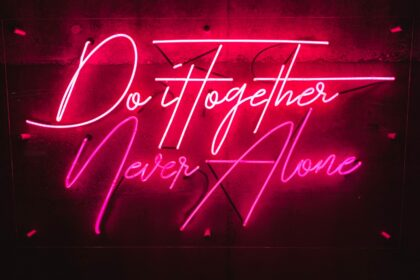 """Pink neon on a black background. Text reads, """"Do it together, never alone."""""""