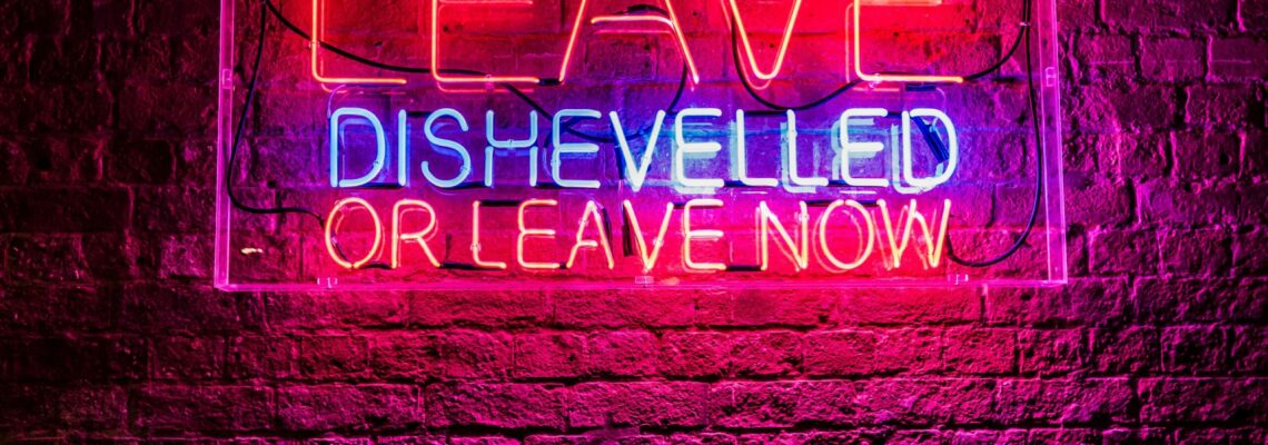 "Red and blue neon on a birkc wass reads ""Leave dishevelled or leave now."""