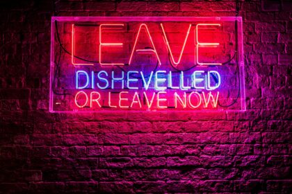 """Red and blue neon on a birkc wass reads """"Leave dishevelled or leave now."""""""