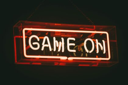 Red neon text on a black background: Game On