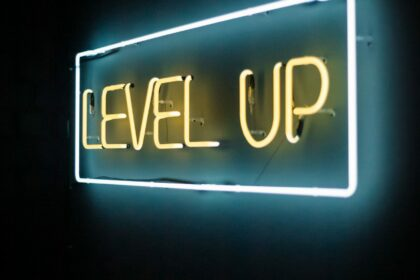 """yellow and white neon text reads """"level up"""" on a brick wall"""