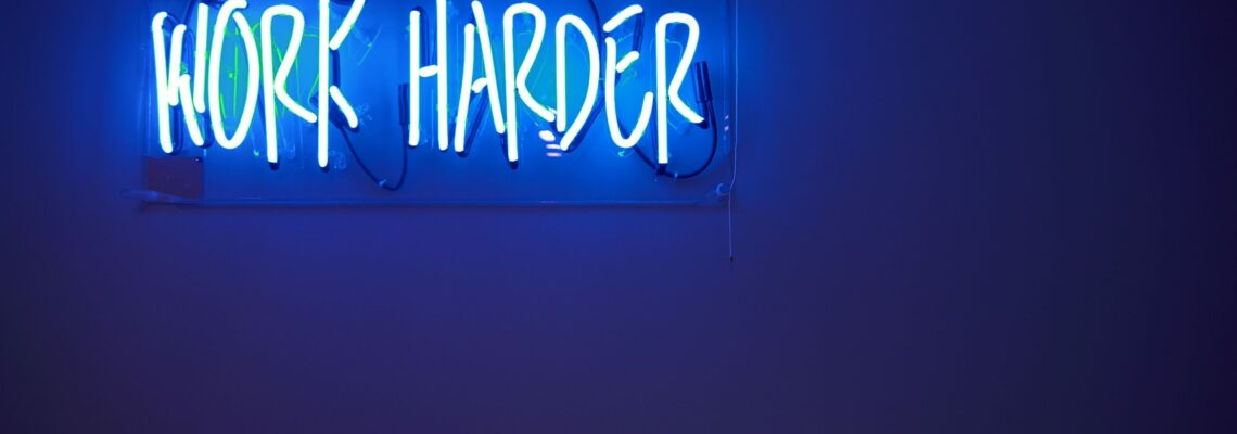 "Blue neon off-set at the top right of a blue wall. Text reads, ""Work harder."""